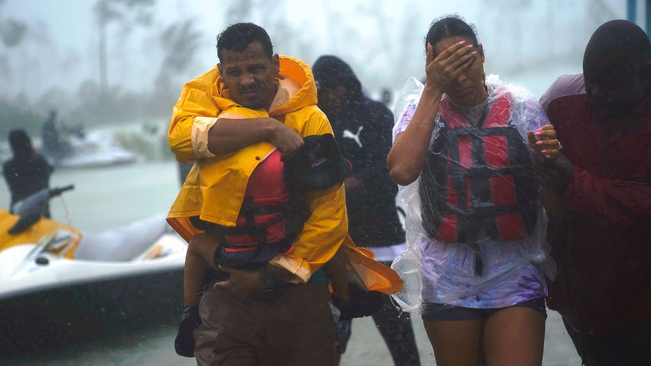 A family is escorted to a safe zone after they were rescued as Hurricane Dorian continues to rain in Freeport, Bahamas, Tuesday, Sept. 3, 2019