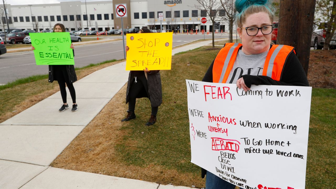 Employee Tonya Ramsay, right, holds a sign outside the Amazon DTW1 fulfillment center in Romulus, Michigan, USA, Wednesday, April 1, 2020. (AP Photo/Paul Sancya)