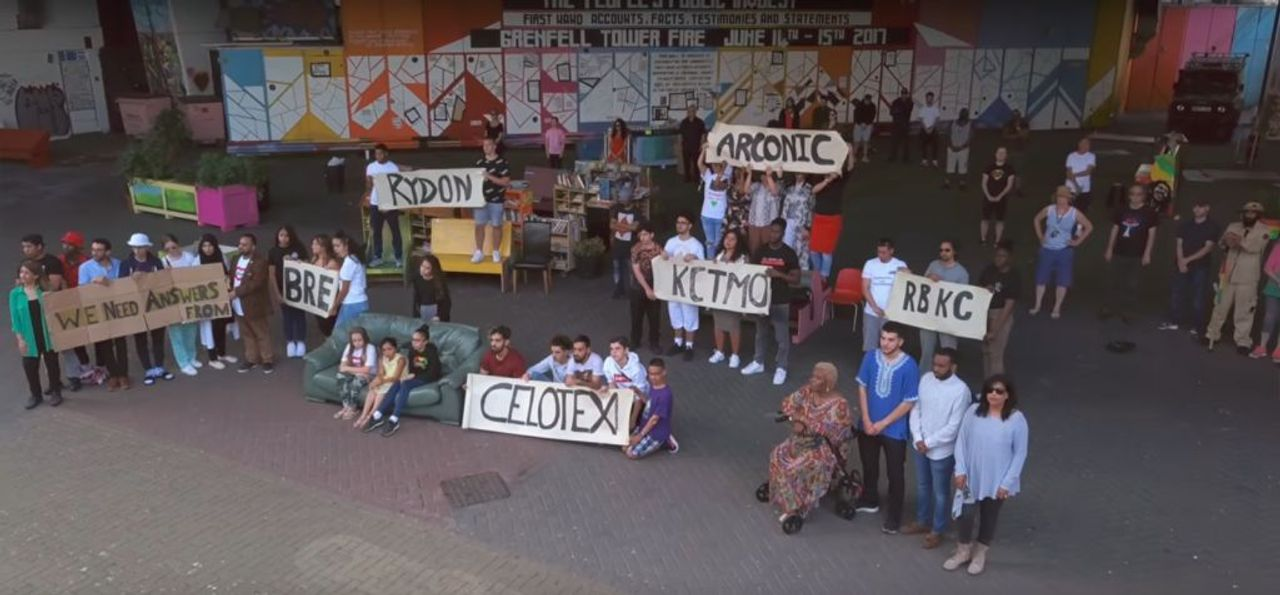 A clip from the video of Ghost of Grenfell 2 with survivors and residents holding up placards naming corporations and authorities involved in the disaster