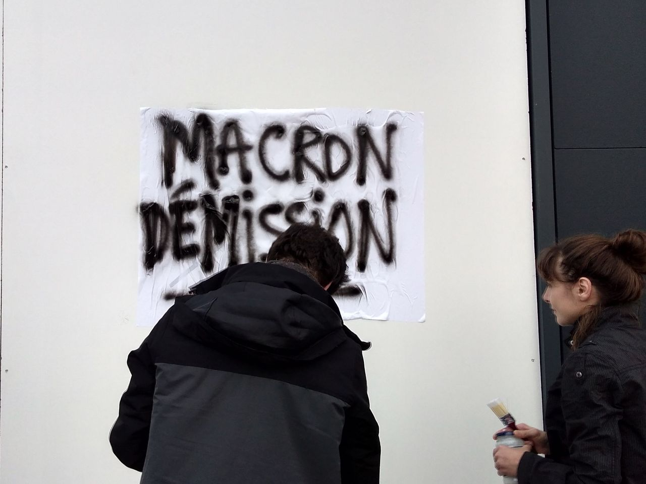 French protesters putting up a poster demanding 'Macron resign'