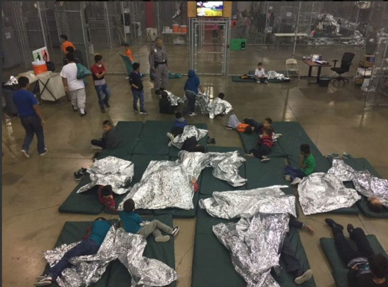 Children sleeping on mats with thermal blankets in a detention center in McAllen, Texas [Credit Customs and Border Protection]