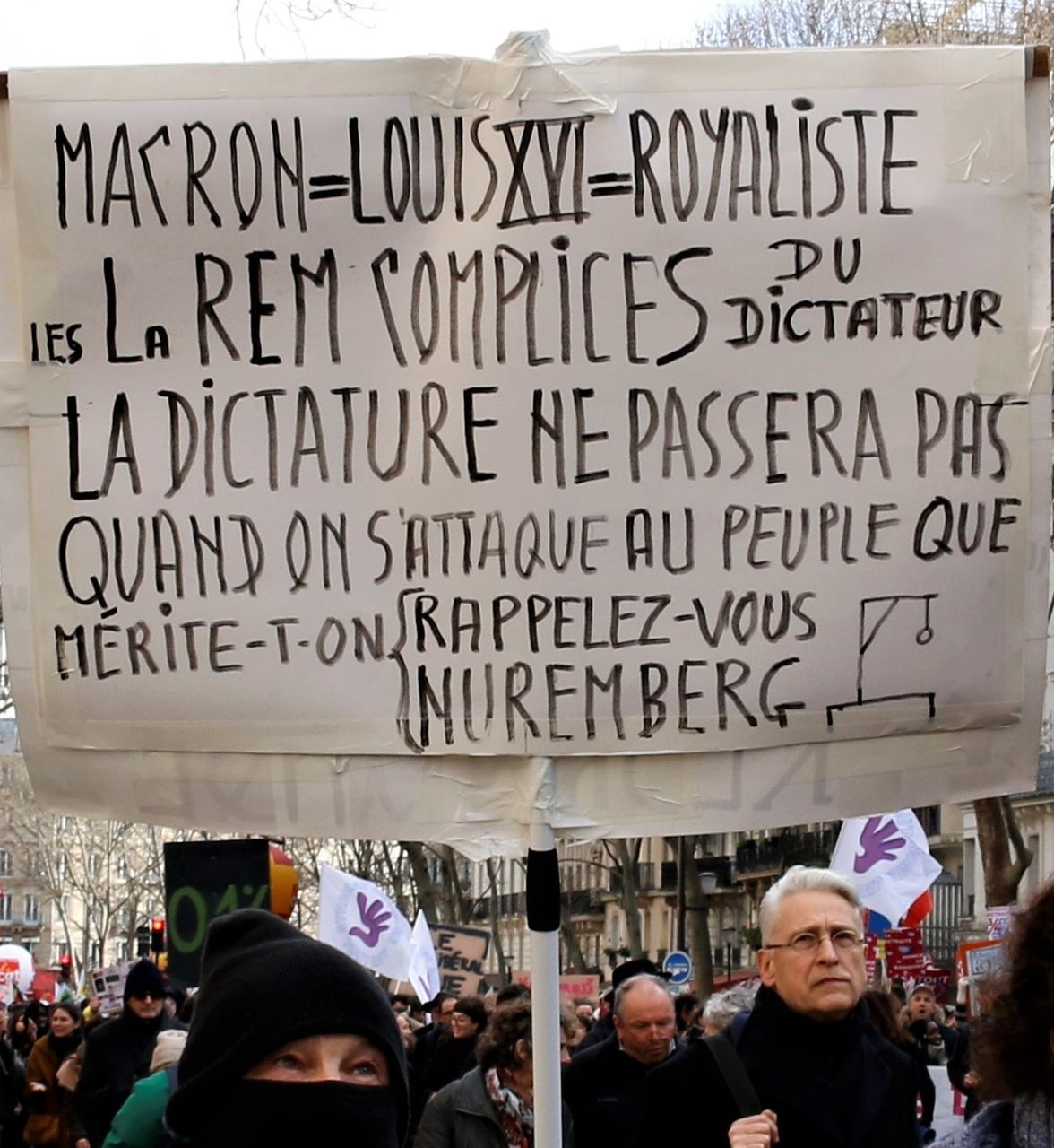 Macron, King Louis XVI, royalist, his party is complicit. Dictatorship will not be tolerated. What do you deserve when you attack the people. Remember the Nuremberg trials, the sign says