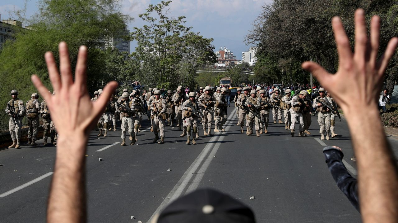 A demonstrator holds up his hands toward advancing soldiers during a protest as a state of emergency remains in effect in Santiago, Chile, Sunday, Oct. 20, 2019. Protests in the country have spilled over into a new day, even after President Sebastian Pinera cancelled the subway fare hike that prompted massive demonstrations. (AP Photo/Esteban Felix)