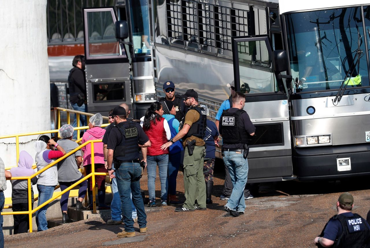 U.S. immigration officials board detained female workers onto a bus destined for a National Guard base at a Koch Foods plant in Morton, Miss. Photo by Rogelio V. Solis via AP
