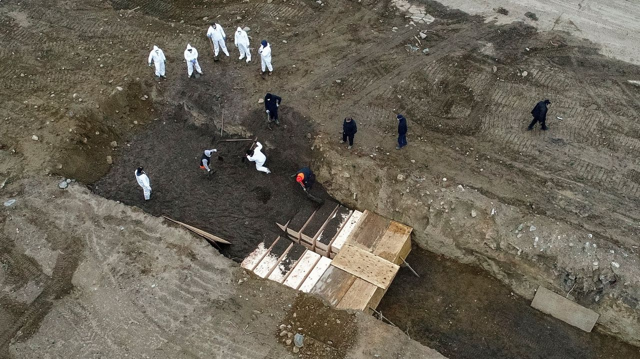Workers wearing personal protective equipment bury bodies in a trench on Hart Island, New York City, USA, April 9, 2020 [Credit: AP Photo/John Minchillo]