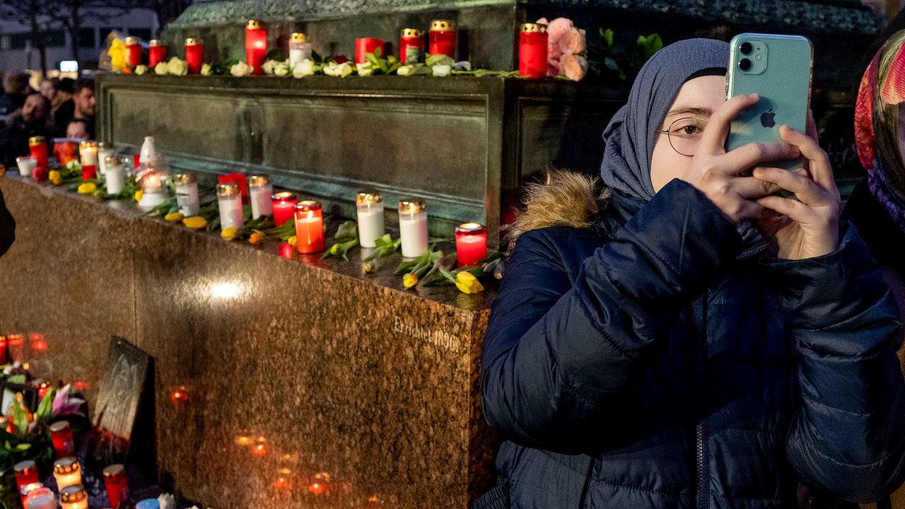 A girl takes a picture near candles at a vigil for the victims of a far-right mass shooting in Hanau, Germany Thursday, Feb. 20, 2020. (AP Photo/Michael Probst)