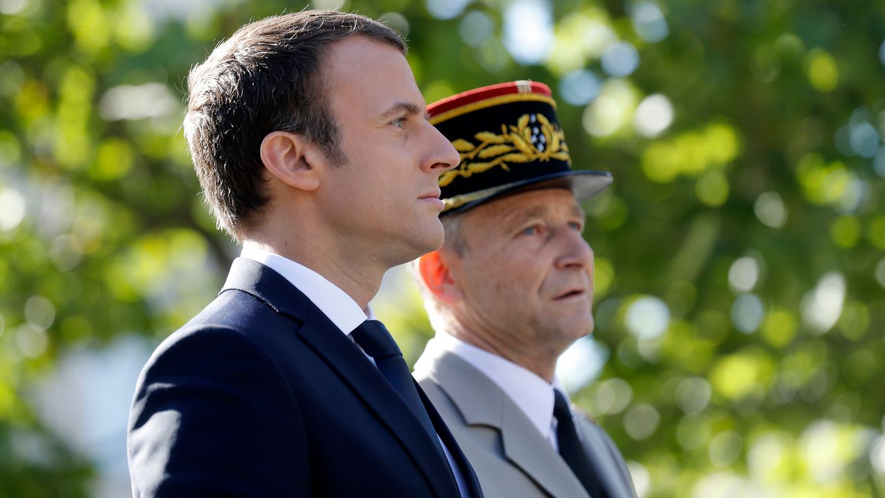 In this July 14, 2017 file photo, French Army Chief of Staff, General Pierre de Villiers, and French President Emmanuel Macron stand in the command car during the annual Bastille Day military parade on the Champs Elysees avenue in Paris [Credit: Etienne Laurent/Pool Photo via AP, File]