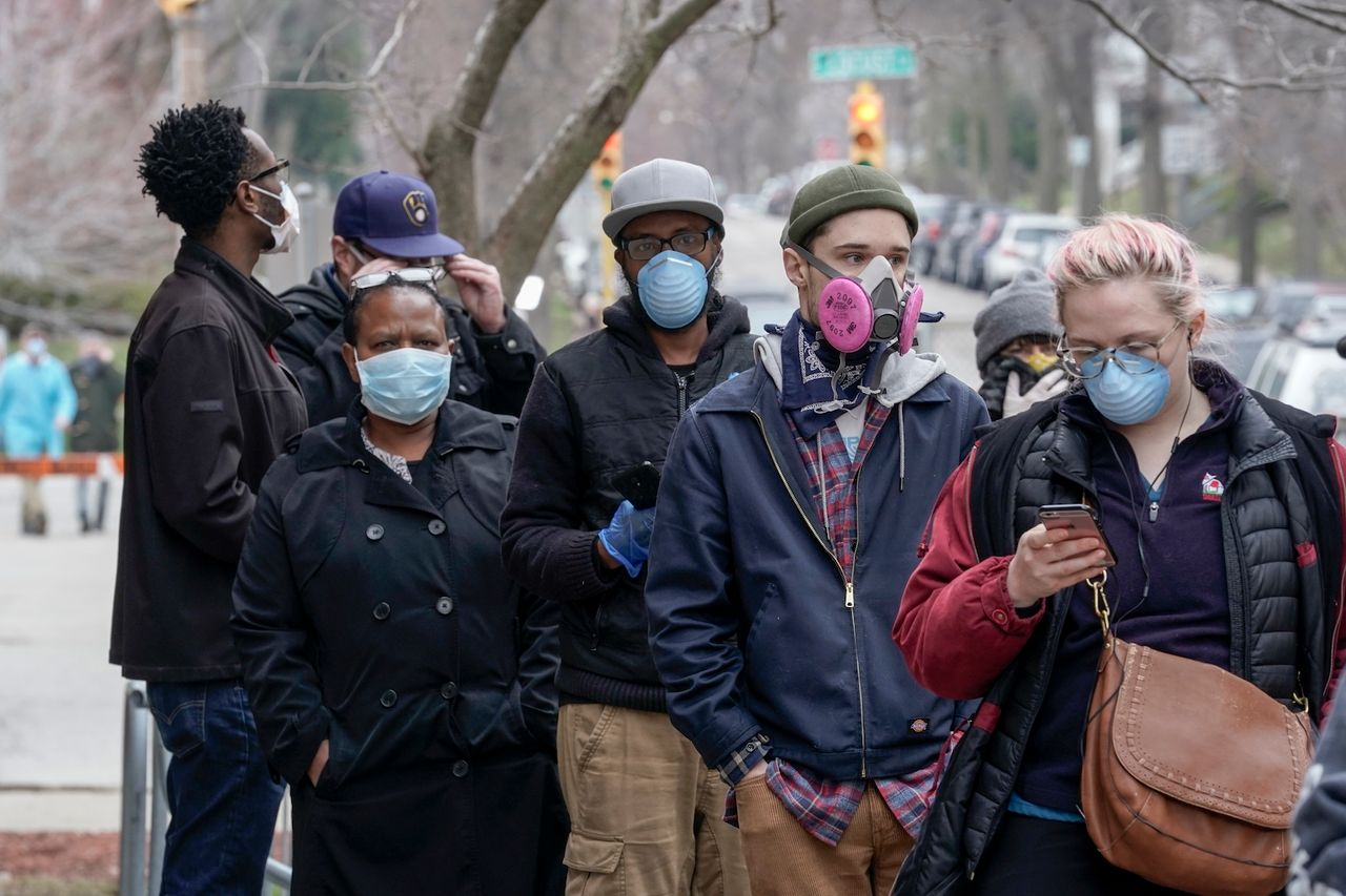 Voters masked against coronavirus line up at Riverside High School for Wisconsin's primary election Tuesday April 7, 2020, in Milwaukee (AP Photo/Morry Gash)