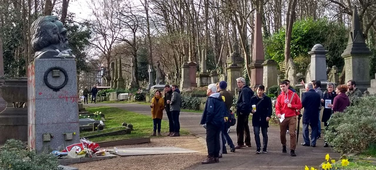 A group of people at Karl Marx's grave in Highgate Cemetery on Saturday