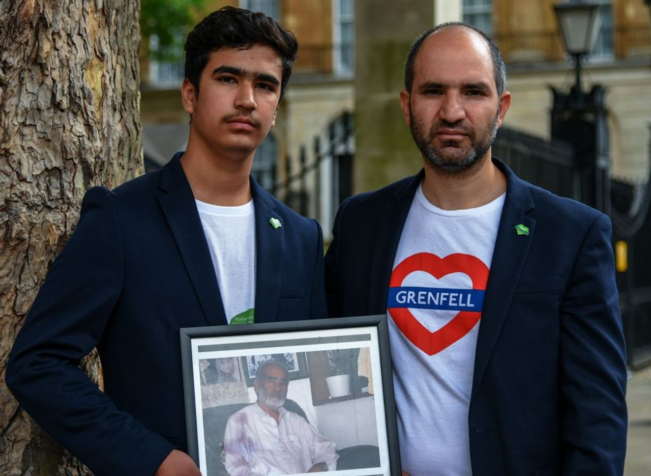 Hamid (right) and his son with a photo of his father, Ali Yawar Jafari