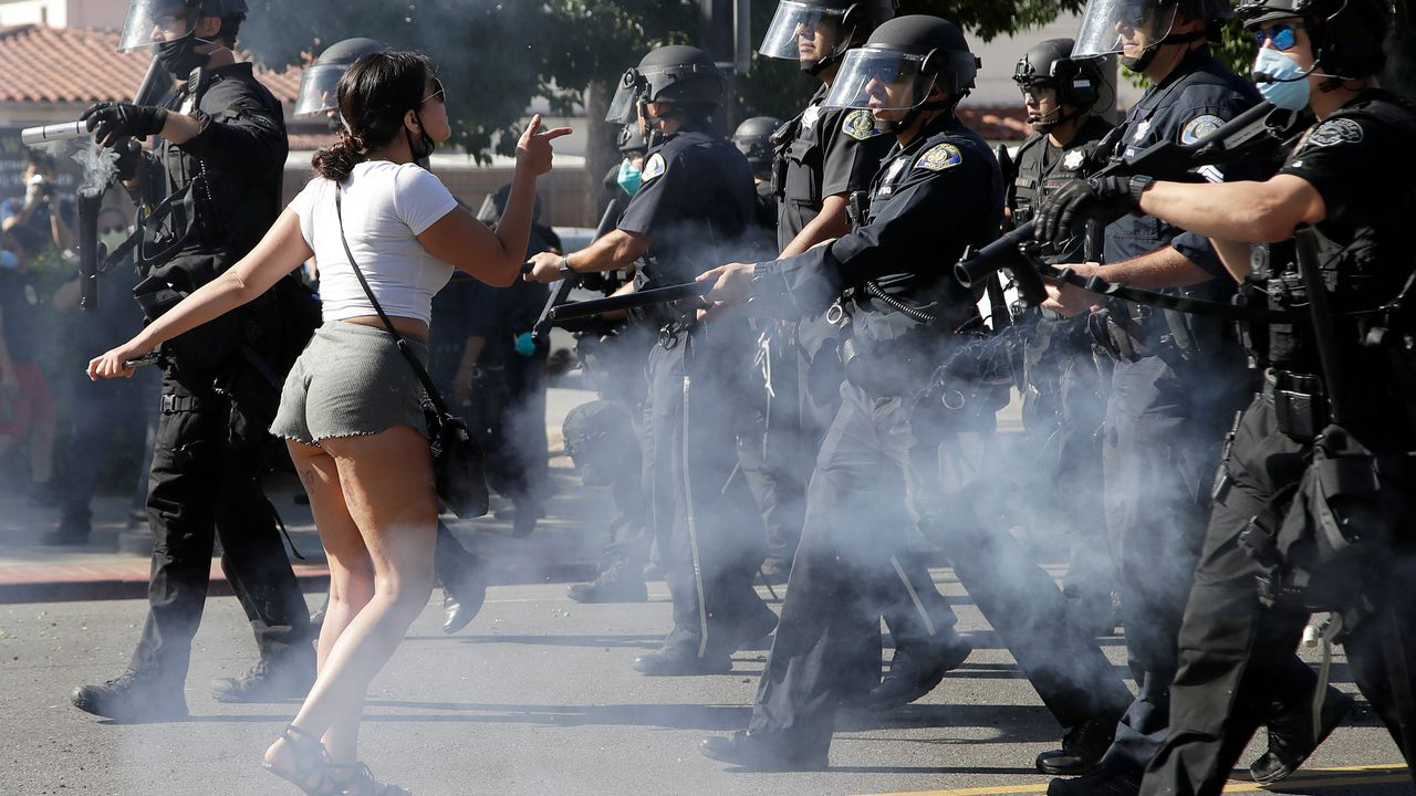 A protester confronts San Jose, USA police as they advance on May 29, 2020, as people demonstrate nationwide in response to George Floyd dying while in police custody [Credit: AP Photo/Ben Margot]